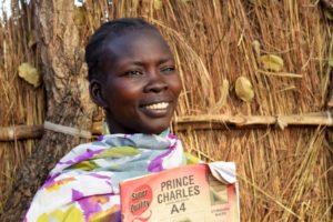 Eteläsudanilainen Nyanjak Nyok seisoo ulkona oppikirja kädessään, hän on yksi Pakolaisavun englannin alkeistason kurssin osallistujista Ugandassa.