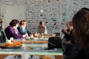 Globaalikasvatuksen koulutuksen osallistujat istuvat pöydän äärellä keskustellen Helinä Rautavaaran museossa.