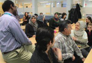 Pakolaisavun omakielisen yhteiskuntaorientaatiokurssin osallistujat istuvat ja keskustelevat luokkahuoneessa ohjaajan kanssa