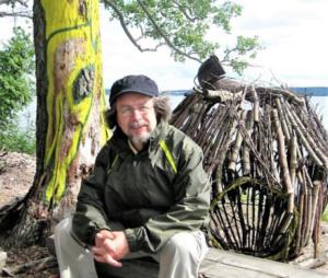 Kari Porra istuu ulkona järvimaisemissa