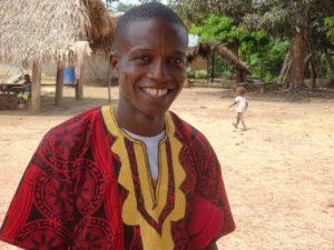 Liberialainen Pakolaisavun fasilitaattori hymyilee kameralle