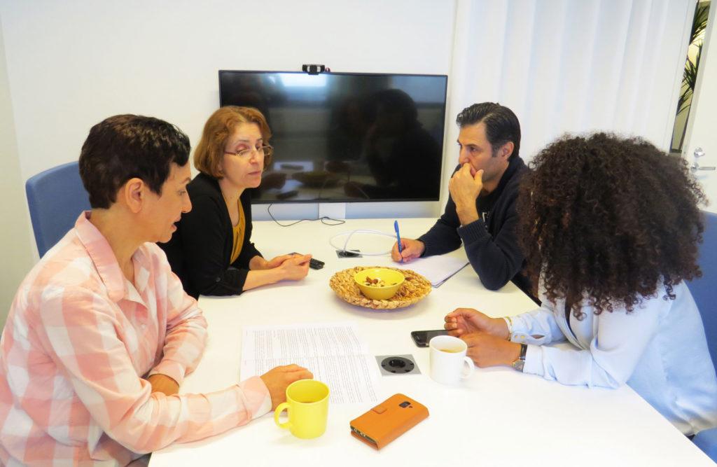 Pakolaisavun omakielisen yhteiskuntaorientaation vetäjien koulutuksessa osallistujat istuvat pöydän ympärillä keskustellen koulutusmateriaaleista