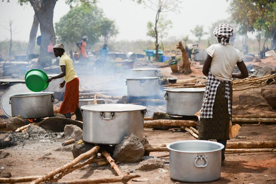 Naiset laittavat ruokaa avotulella Adjumanin pakolaisasutusaleelta Ugandasta
