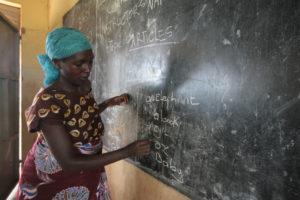 Nainen kirjoittaa liitutaululle Pakolaisavun englannin kielen tunnilla Ugandassa