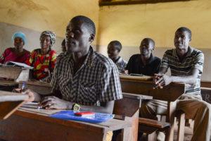 Aikuisopiskelijoita oppitunnilla Ugandassa