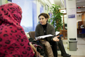 Pakolaisavun työntekijä Maryam Fathollahi opastaa asiakasta.
