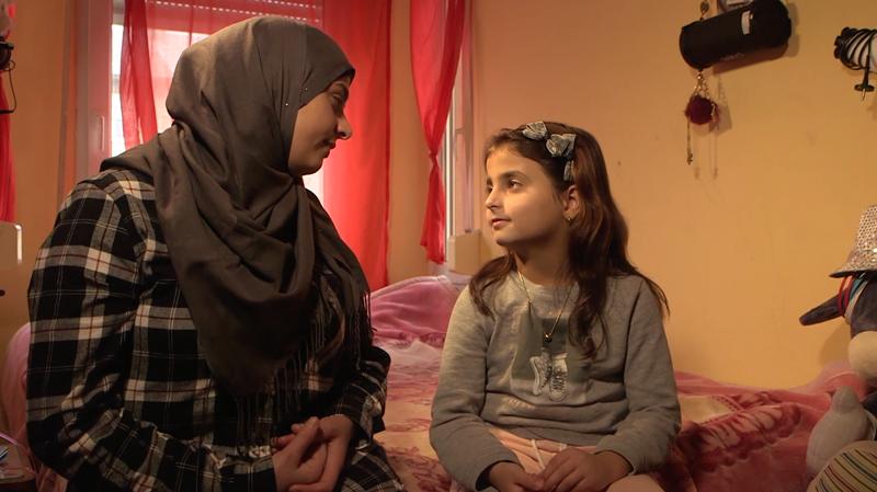 7-vuotias Syyriasta perheineen paennut Rahr istuu sängyllään äitinsä kanssa.