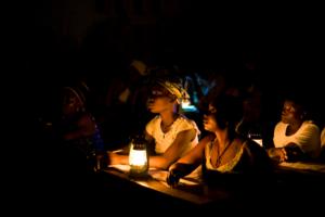 Naisoppilaat istuvat Suomen Pakolaisavun oppitunnilla lyhdyn valossa