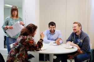 Pakolaisavun vertaistoimintaan osallistuvat keskustelevat ja nauravat pöydän ääressä