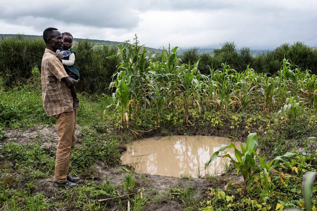 Okom Abwolla seisoo pellolleen kaivaman vesikuopan vieressä Nakivalen pakolaisasutusalueella