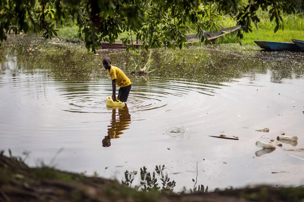 Poika kerää vettä saastuneesta järvestä pakolaisasutusalueella Ugandassa