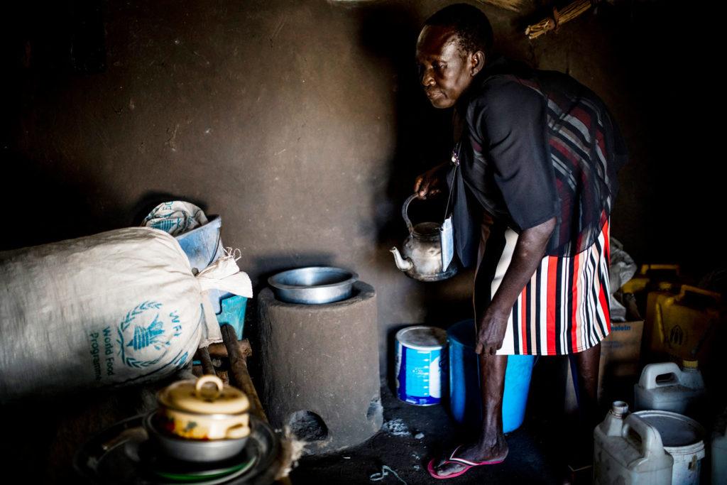 Suomen Pakolaisavun kursseilla käynyt pakolaisnainen tekee ruokaa ekoliedellä hämärässä