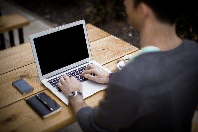 Henkilö kirjoittaa tietokoneella
