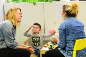 Pakolaisavun ohjaaja Jenny Joensuu keskustelee maahanmuuttajataustaisen äidin kanssa hänen lapsensa leikkiessä vieressä