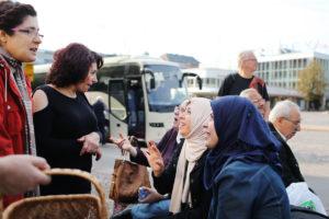 Maahanmuuttajataustaisia ihmisiä keskustelemassa vilkkaasti ulkona