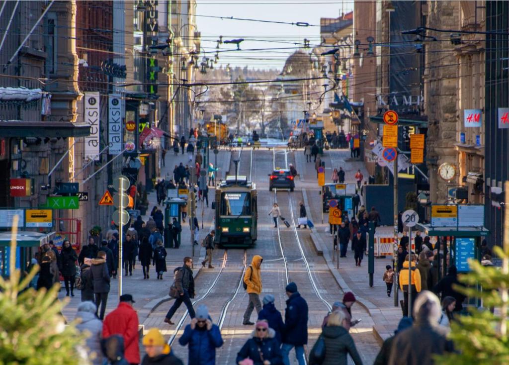 Ihmisiä ja raitiovaunu vilkkaalla kadulla