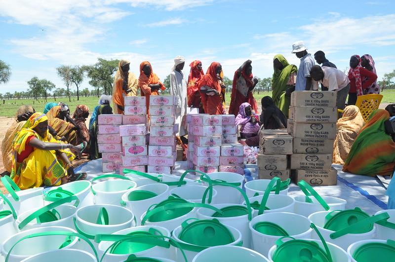 Sudanin pakolaisleirillä joukko ihmisiä on kerääntynyt jaettavien tarvikkeiden, kuten vesiämpäreiden ja elintarvikkeiden, ympärille.