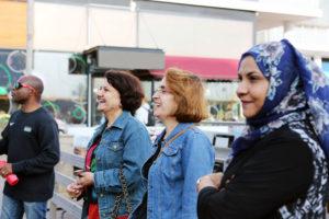 Neljä iloista ihmistä seisoo rakennuksen edustalla