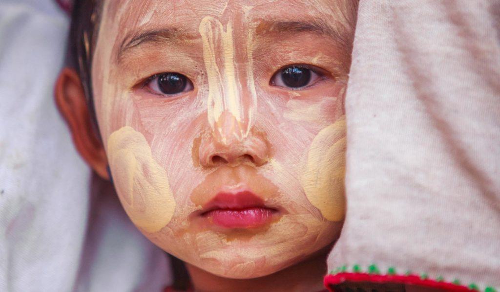 Myanmarilaisen lapsen, jonka kasvot ovat maalattu, katsoo kameraan