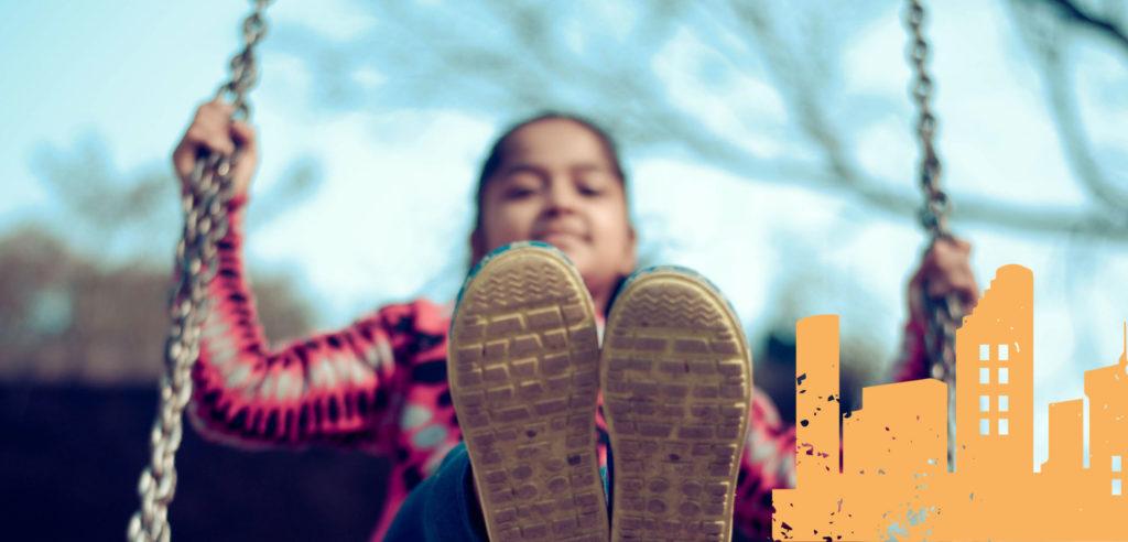 Tyttö keinuu kengät kohti kameraa.