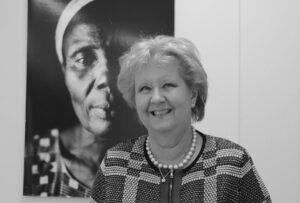 Pakolaisavun hallituksen edesmennyt puheenjohtaja Marjatta Rasi hymyilee valokuvataulun edessä.