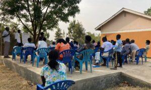 Kuva on Ugandan talouslukutaidon kurssin opetustilateesta. Joukko ihmisiä istuu sinisillä tuoleilla ulkotilassa ja katsovat opetustaululle