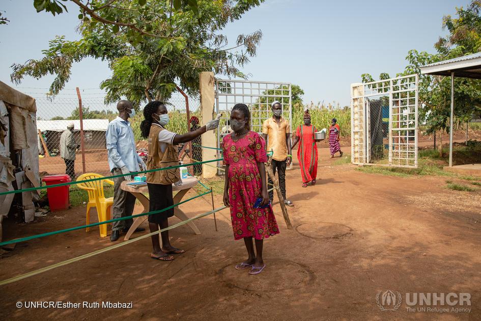 Kuvassa Ugandalaiselta naiselta mitataan kuume. Taustalla näkyy hiekkaa, muita ihmisiä joilla on hengityssuojat ja vehreitä puita.