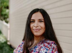 Vuoden pakolaisnainen 2021 Sara Al Husaini hymyilee kameralle kukkamekossa.