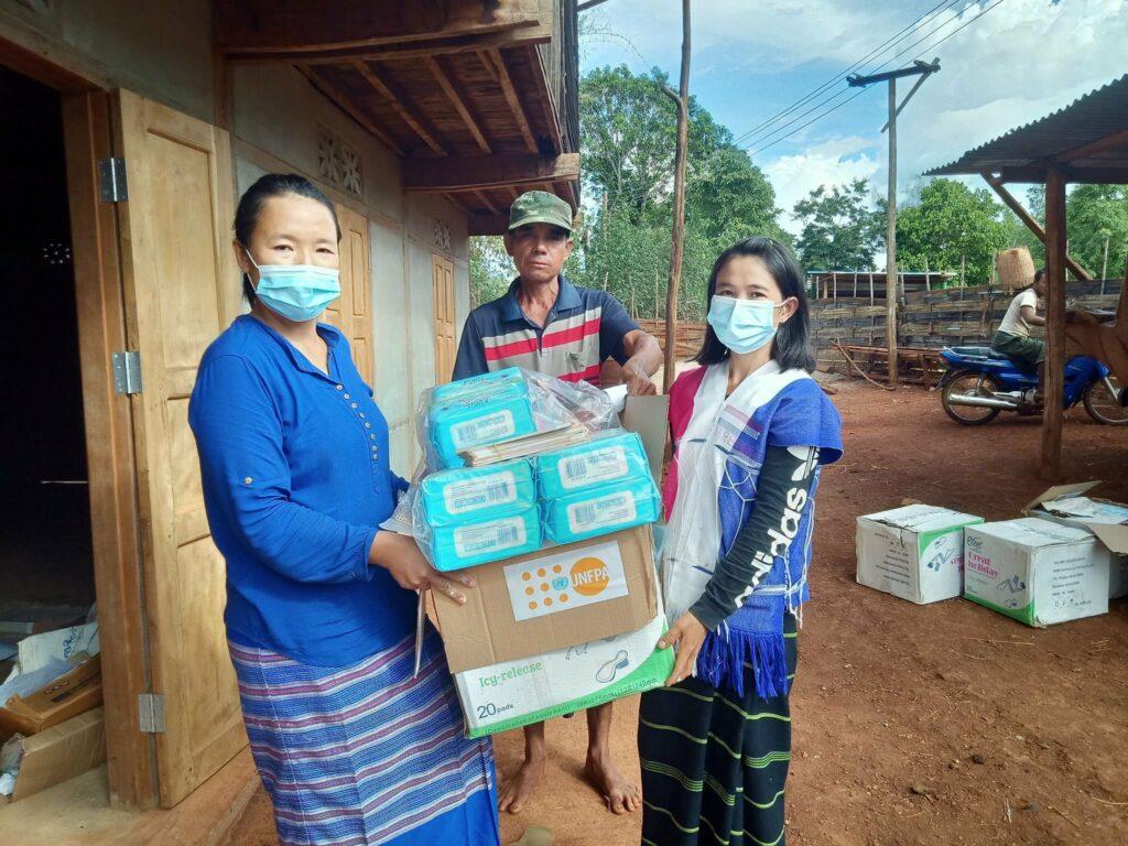 Kuvassa kolme henkilö katsoo kameraan ja pitelee käsissään jaettavia hygieniatarvikkeita. Kahdella henkilöistä on yllään hengitysmaskit.