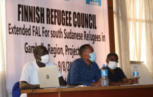Kolme miestä istuu pöydän ääressä takanaan Finnish Refugee Council -banneri.