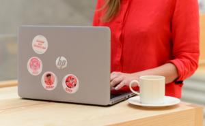 Henkilö kirjoittaa tietokoneella, jonka vieressä on kahvikuppi.