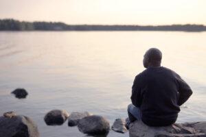 Mies istuu kivellä järven rannalla selkä kameraan päin.