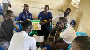 Kuusi Ugandan koulutukseen osallistuvia aikuista istuu pöydän äärellä.