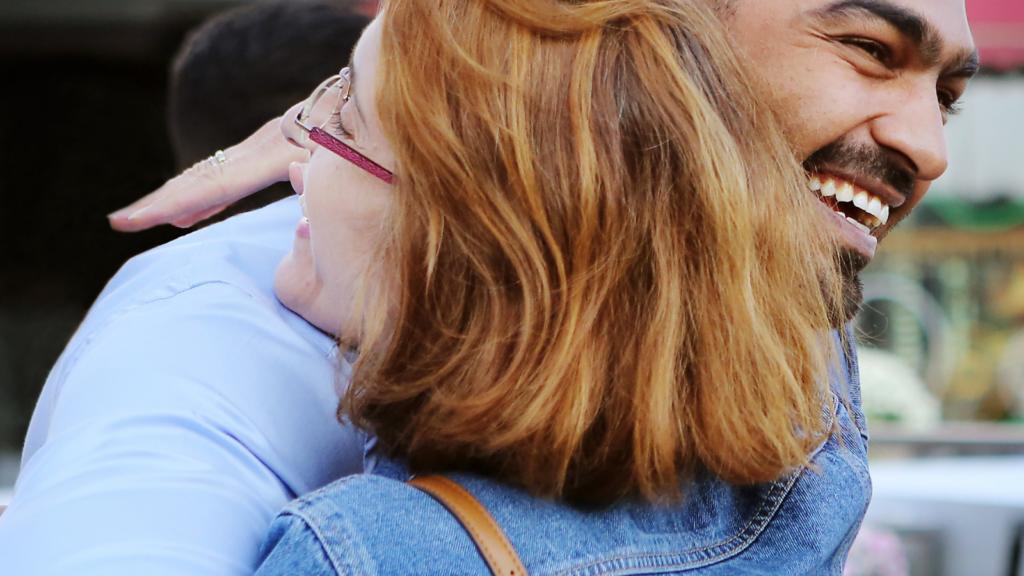 Hymyilevä mies halaa naista.